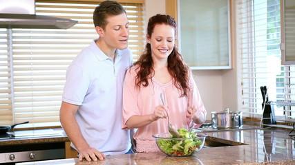 Smiling woman mixing a salad