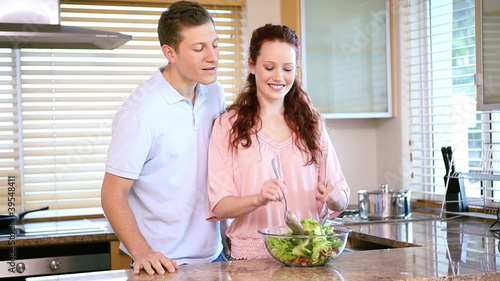 Smiling woman mixing a salad