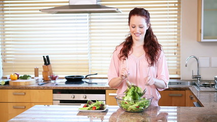 Young woman mixing a salad
