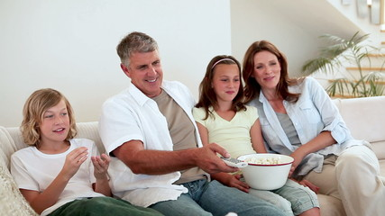 Family eating popcorn while watching the television