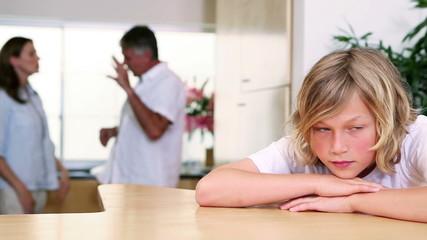 Little boy listening to his parents quarreling