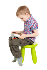 boy with a Tablet PC sitting on a green children's chair