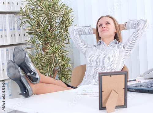 business woman at the office with her feet on the desk