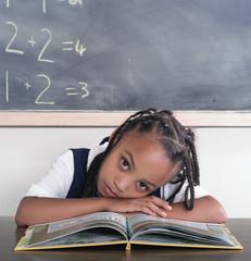 School girl laying on book