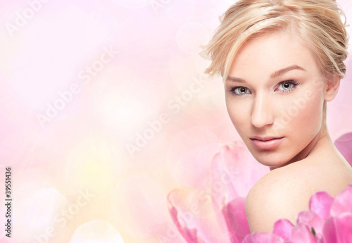 Young blond woman in flower petals