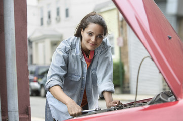 Young woman working on vehicle