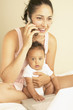 Young mother talking on phone with baby in arms