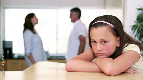 Little girl listening to her parents quarreling