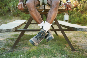 Low section of man sitting on picnic table