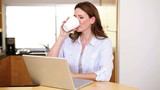 Woman drinking a coffee in front of her laptop