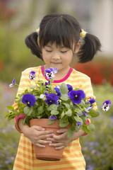 Girl holding pot of flowers