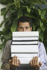 Man holding stack of notebooks