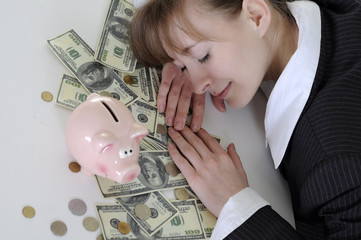 Business woman sleeping on a table in money