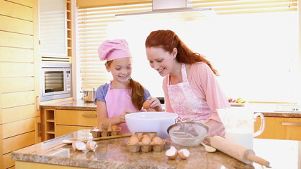Smiling mother and daughter cooking