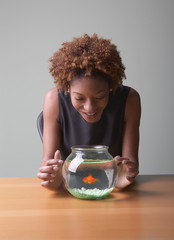 Woman looking at goldfish in bowl