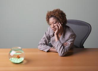 Sad businesswoman watching goldfish
