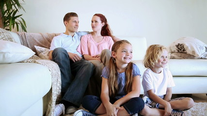 Siblings sitting on the floor while watching tv with their parents behind them