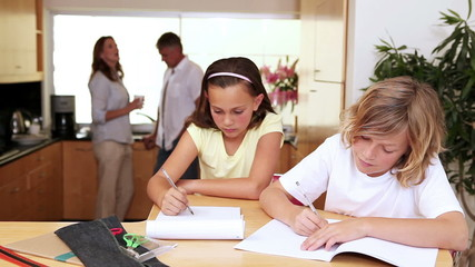 Brother and sister doing homework in the kitchen with parents behind them