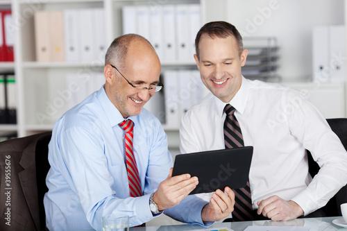 zwei geschäftsleute schauen auf tablet-pc und haben spaß