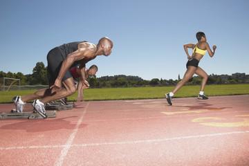 Three people racing on track