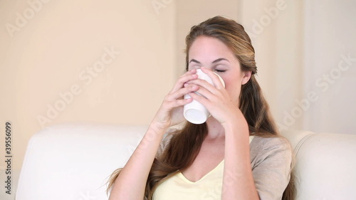A woman sitting while drinking coffee