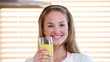 Smiling woman drinking orange juice