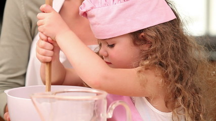 Girl preparing dough with her mother