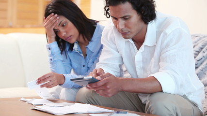 Frustrated couple calculating their expenses