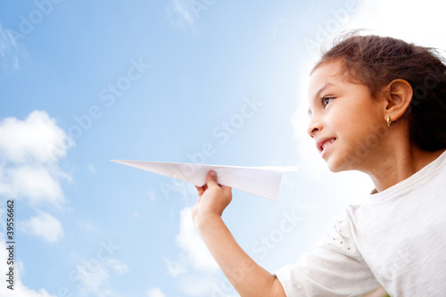 Girl holding a paper airplane