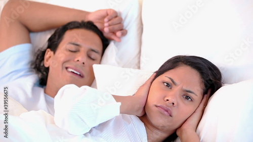 Annoyed woman lying next to her snoring boyfriend