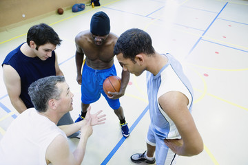 High angle view of coach talking to basketball team
