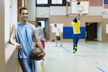 Man holding basketball with team warming up behind him