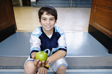 Portrait of boy on steps holding apple