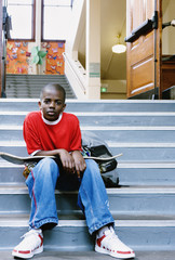 Portrait of boy with skateboard on school stairs