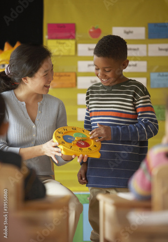 Female teacher helping student to tell time