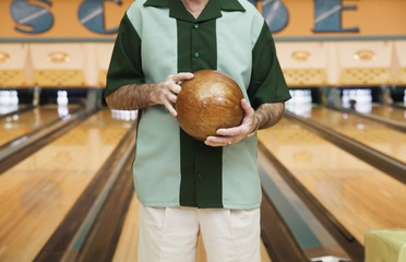 Midsection of man holding bowling ball