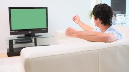 Man watching the television while speaking