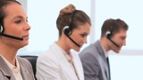 Smiling business people working with headsets