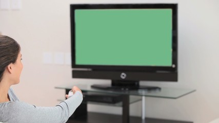 Brunette woman holding a remote