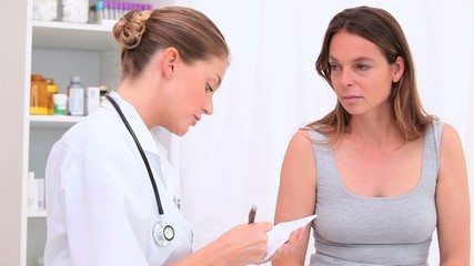 Brunette woman talking with her doctor