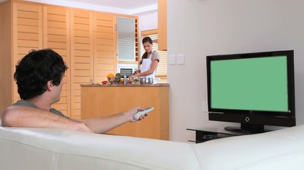 Man watching the television while his wife is preparing a meal