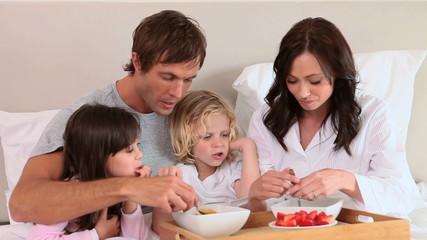 Smiling family eating their breakfast