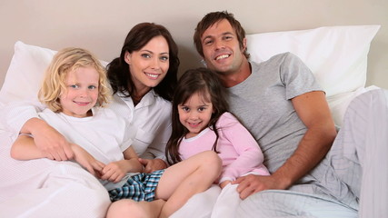 Smiling family lying in a bed