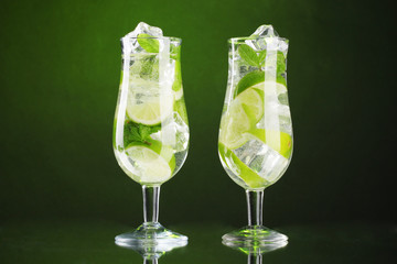 glasses of cocktails with lime and mint on green background
