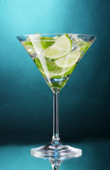 glass of cocktail with lime and mint on blue background