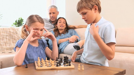 Serious siblings playing chess