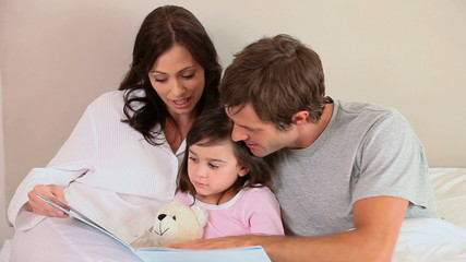 Happy family reading a book aloud