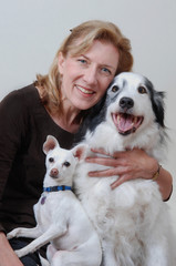 Smiling woman hugging 2 dogs