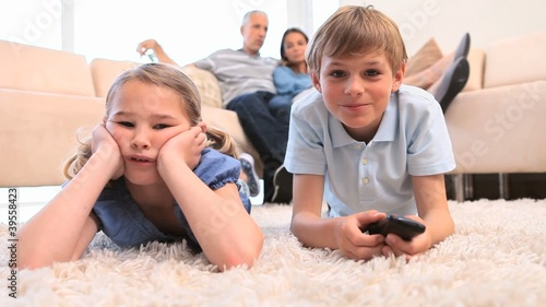 Children watching the television with their parents