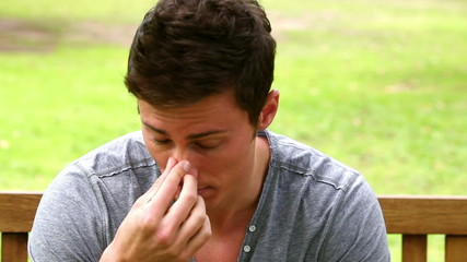 Disappointed man putting his face in his hands while shaking his head as he sits on a bench
